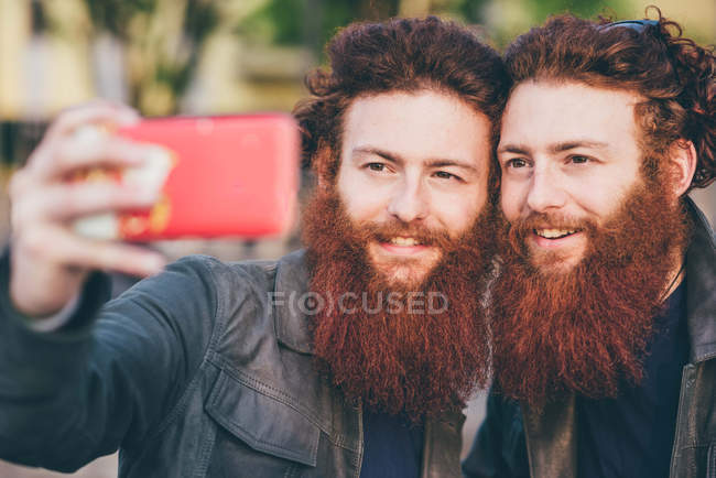 Young male hipster twins with red hair and beards taking smartphone selfie — Stock Photo