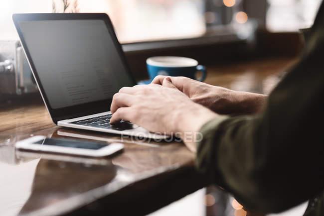 Uomo che lavora sul computer portatile al bar — Foto stock