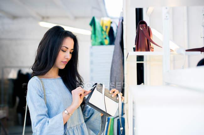 Frauen in der Boutique Blick auf Preisschild auf Handtasche — Stockfoto