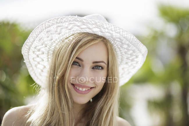 Ritratto di bella giovane donna bionda con cappello di paglia in città — Foto stock