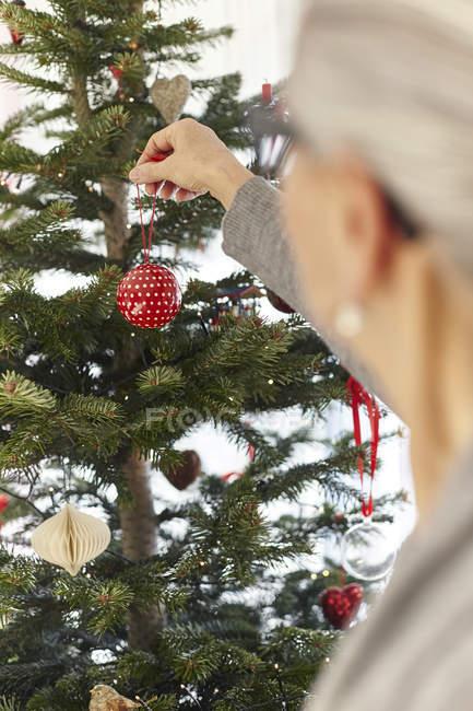 Senior woman putting bauble on christmas tree — Stock Photo