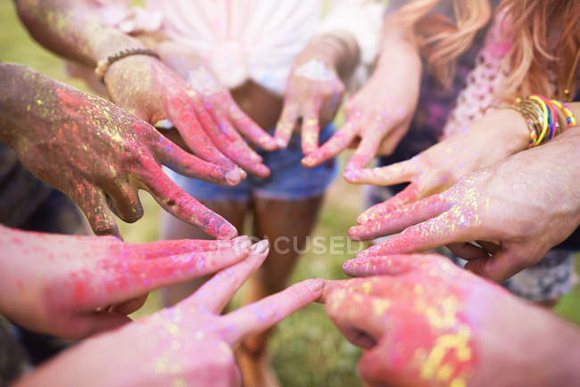 Group of friends at festival, covered in colourful powder paint, connecting fingers with peace signs, close-up — Stock Photo