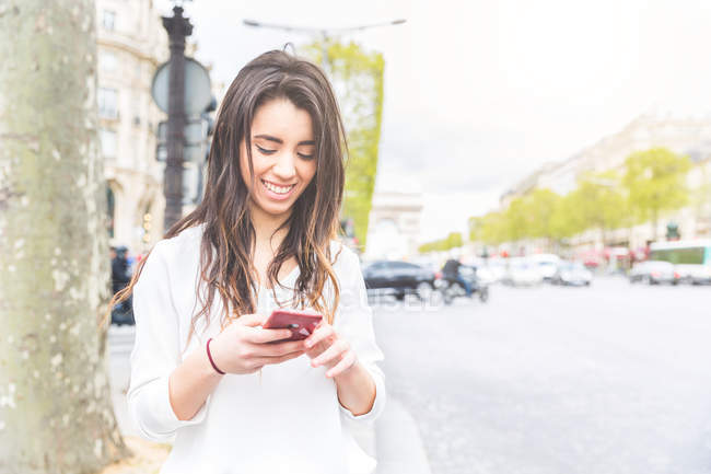 Young woman on Champs Elysees reading smartphone texts, Paris, France — Stock Photo