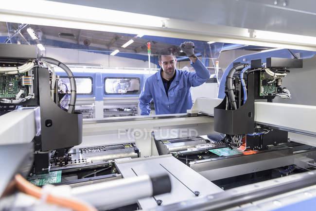 Робот, размещающий компоненты на плате на заводе по сборке печатной платы — стоковое фото