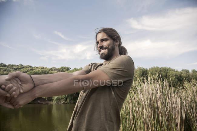 Молодой человек рекой, взявшись за руки, склоняется обратно улыбается — стоковое фото