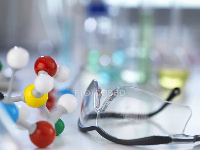 Safety glasses and molecular model on laboratory bench — Stock Photo