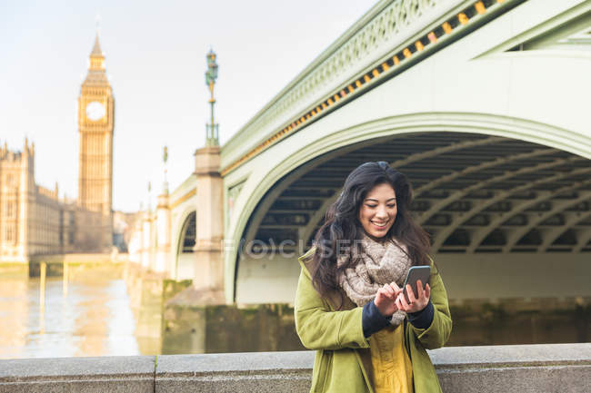 Young woman in front of Westminster bridge and Big Ben looking down using smartphone smiling, Thames river, London, UK — Stock Photo