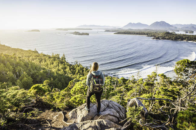 Elevated view of female hiker looking out from coastal forest, Pacific Rim National Park, Vancouver Island, British Columbia, Canada — Stock Photo