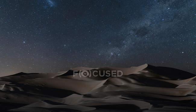 View of sand dunes under starry night sky — Stock Photo