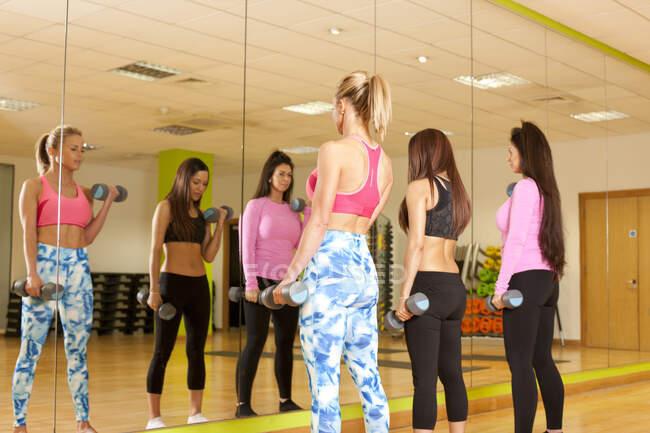 Image miroir de femmes en gymnastique utilisant des haltères — Photo de stock