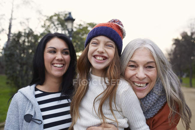 Portrait of mother and daughter and grandmother looking at camera smiling — Stock Photo