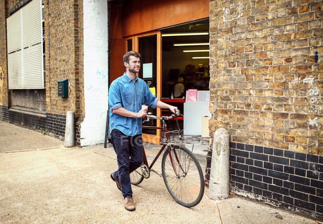 Jovem carregando café e bicicleta de rodas após oficina — Fotografia de Stock