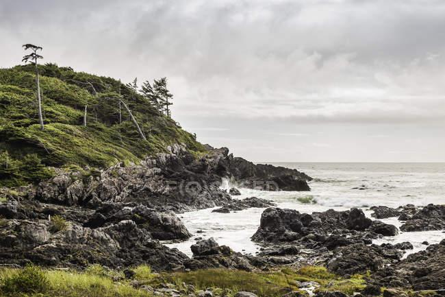 Скелястий берег з хвилями прибою під хмарного неба — стокове фото