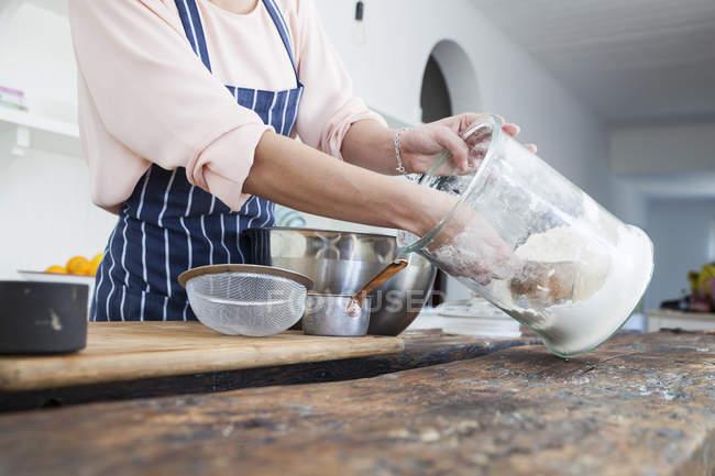 Куповані образ жінки, черпаючи борошно з банку на кухонного столу — стокове фото