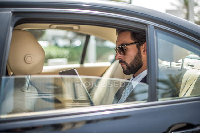 Young businessman using digital tablet in car backseat, Dubai, United Arab Emirates — Stock Photo