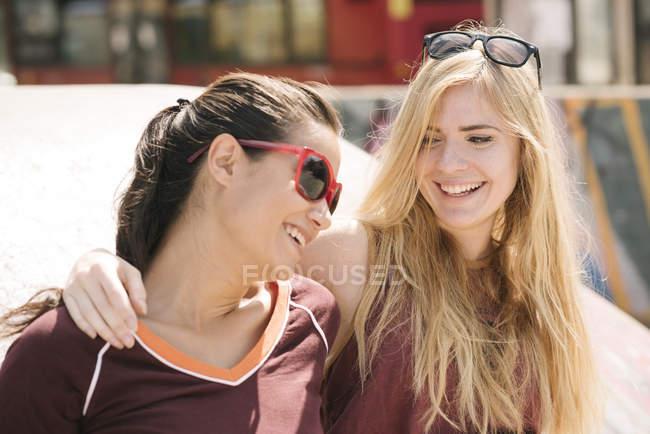 Two female skateboarding friends laughing in skatepark — Stock Photo