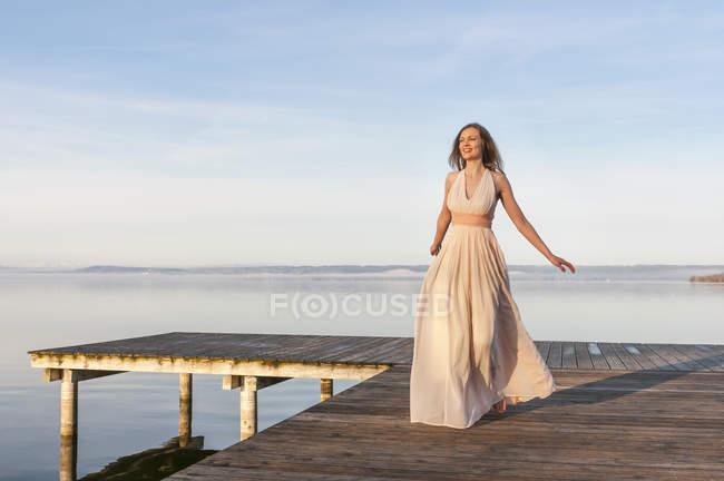 Повна довжина погляд жінки на дерев'яні пристань за океан носити довгі шифон плаття, дивлячись away посміхається — стокове фото