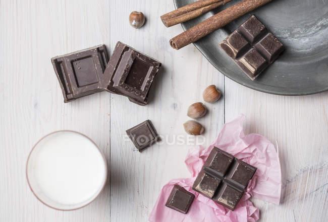 Вид зверху шоколадом кубів, горіхи, палички кориці, склянку молока на стіл — стокове фото