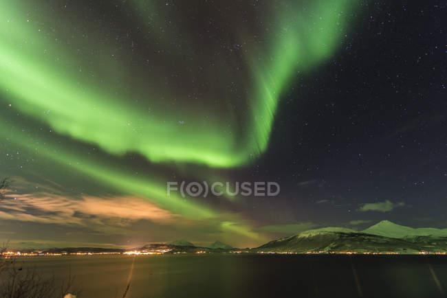 Северное сияние освещало небо над гаванью Тромсо — стоковое фото