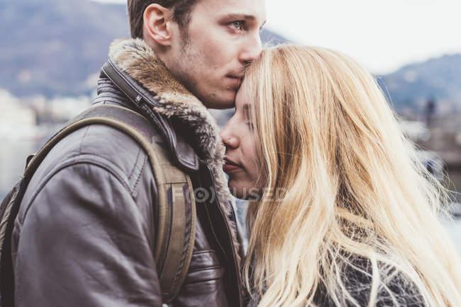 Jovem romântico beijando namoradas testa, Lago de Como, Itália — Fotografia de Stock