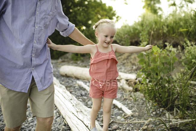 Девушка с отцом шагает вдоль ствола дерева на озере Онтарио, Ошава, Канада — стоковое фото