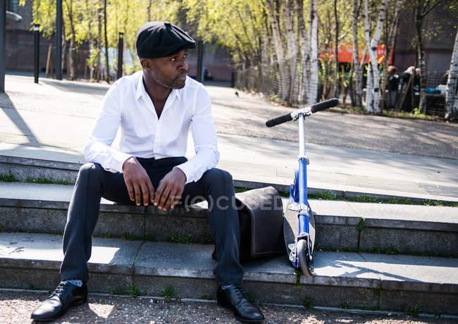 Businessman beside scooter on steps, London, UK — Stock Photo