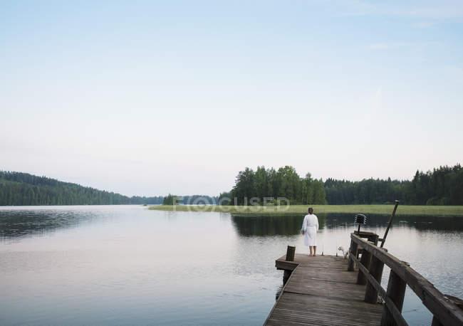 Mulher vestindo roupão de banho com cotão de tulear cão olhando para fora do cais do lago, Orivesi, Finlândia — Fotografia de Stock