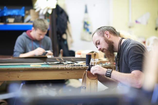 Чоловічий працівник в шкіра семінар, пошиття вгору шви навколо пряжкою — стокове фото