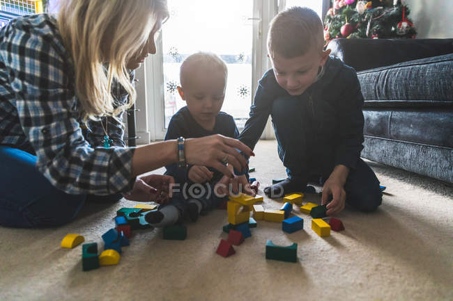 Mother and two sons playing together with building blocks — Stock Photo