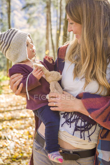 Mère et chéri avec le jouet câlin dans la forêt — Photo de stock