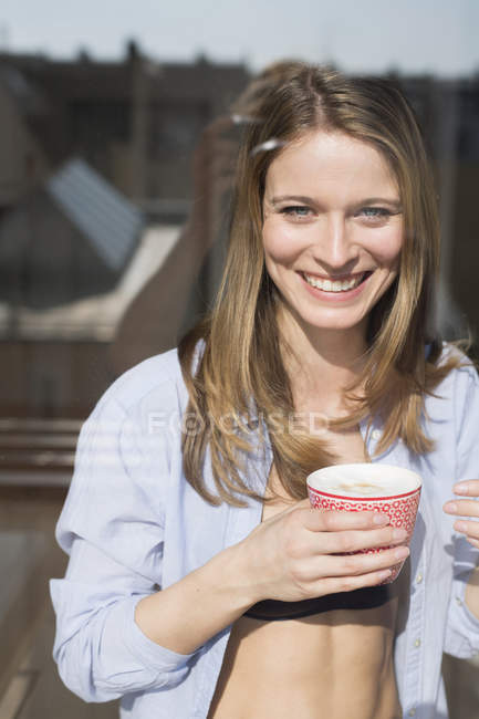 Portrait of beautiful woman wearing open shirt holding coffee  at window — Stock Photo