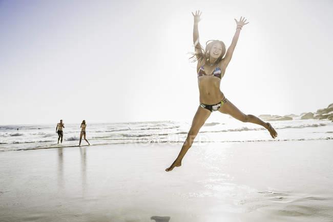 Взрослая женщина в бикини, прыгающая в воздухе на пляже, Кейптаун, ЮАР — стоковое фото