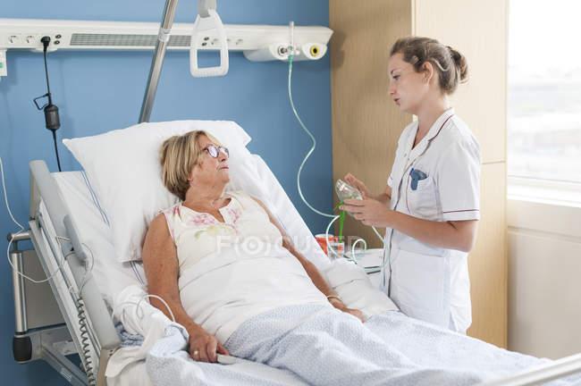 Enfermeira que cuida do paciente no leito hospitalar — Fotografia de Stock