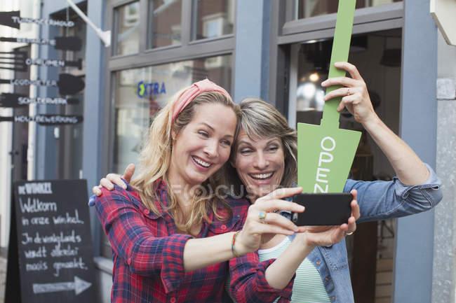 Mujeres frente a la tienda sosteniendo letrero abierto tomando selfie con teléfono inteligente - foto de stock