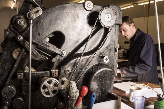 Young male printer operating printing machinery in printing press workshop — Stock Photo