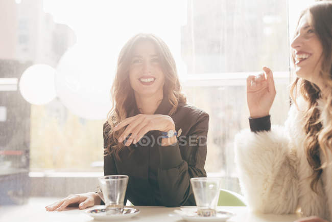 Twin sisters dans café, sourire — Photo de stock