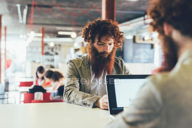 Близнецы-хипстеры, работающие на ноутбуке в офисе — стоковое фото