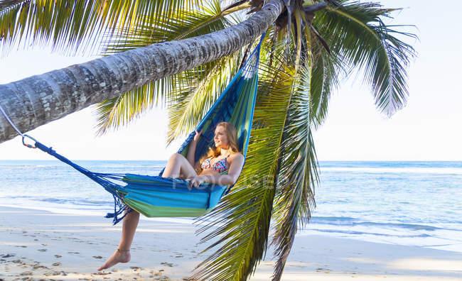 Молода жінка лежить в гамаку, Дерево пальми, Домініканська Республіка, Карибського моря — стокове фото