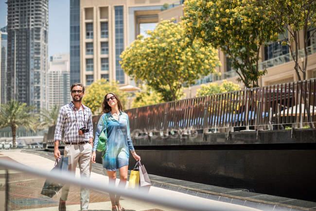 Couple se promenant sur le trottoir, porter les sacs, Dubai, United Arab Emirates — Photo de stock
