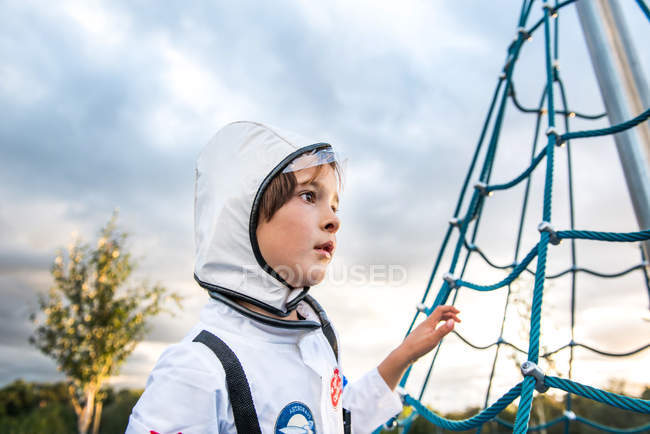 Portrait of boy in astronaut costume gazing by playground climbing frame — Stock Photo