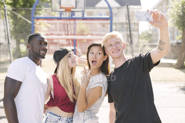 Four adult friends posing for smartphone selfie on basketball court — Stock Photo