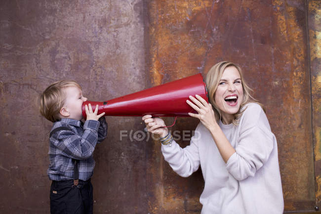 Young boy speaking into megaphone, woman holding megaphone to her ear — Stock Photo