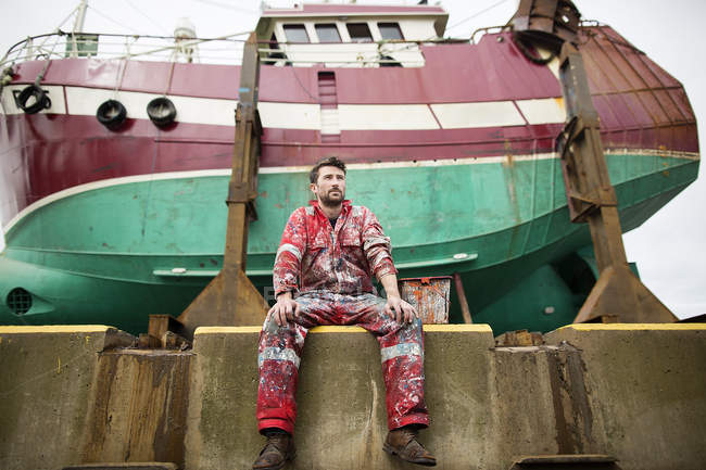 Male ship painter sitting in front of fishing boat on drydock — Stock Photo