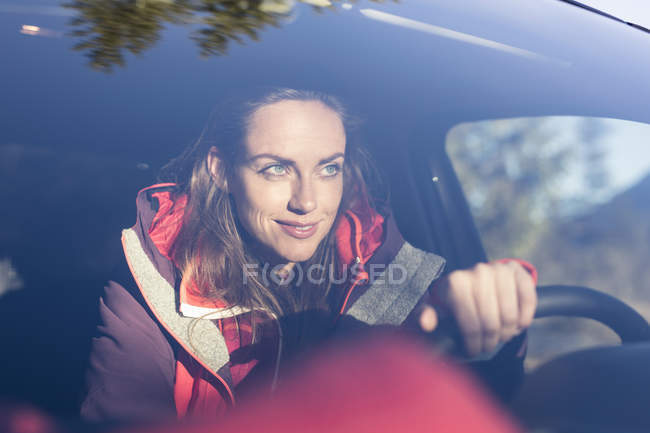 Windscreen view of woman driving car — Stock Photo