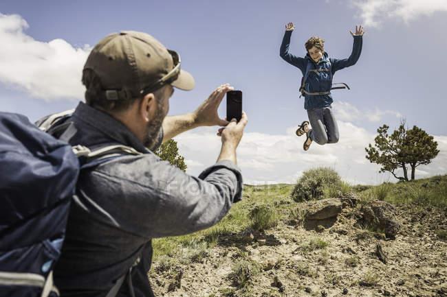 Père de photographier le fils adolescent saut mi air sur randonnée, Cody, Wyoming, Usa — Photo de stock