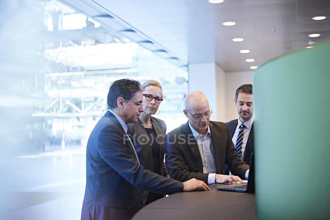 Réunion d'affaires et de femme autour de l'ordinateur portatif dans le bureau — Photo de stock