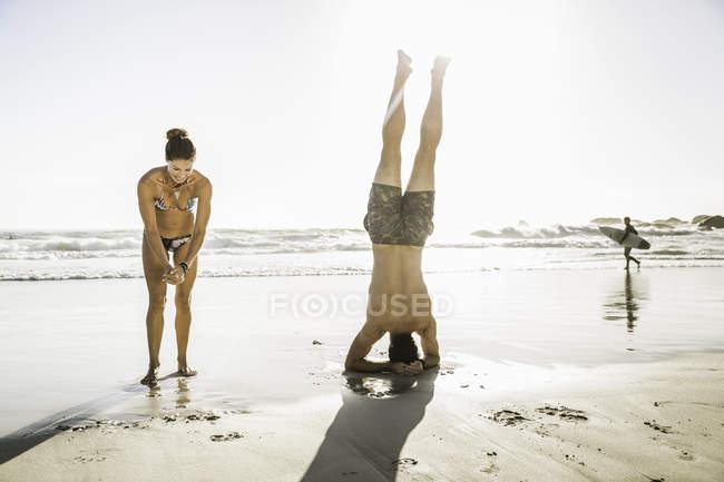 Взрослый мужчина с девушкой, стоящий на голове на пляже, Кейптаун, Южная Африка — стоковое фото