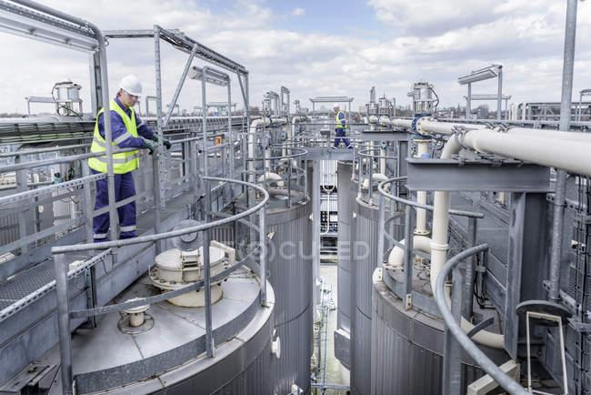 Travailleurs sur le dessus de l'usine de traitement dans l'usine de mélange d'huile — Photo de stock