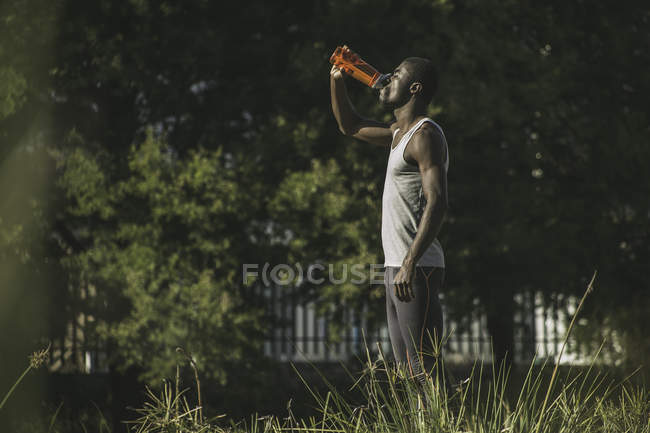 Side view man in field drinking from plastic bottle — Stock Photo