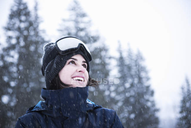 Portrait of young woman wearing ski goggles looking up at snow, Brighton Ski Resort outside of Salt Lake City, Utah, USA — Stockfoto